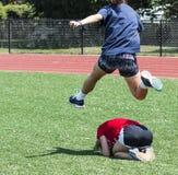 Atleta hurdling jej współczłonka drużyny dla zabawy zdjęcie stock
