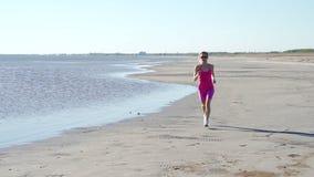 Atleta independiente de la mujer joven que corre en la playa que ejercita al corredor femenino que esprinta el entrenamiento en f almacen de metraje de vídeo