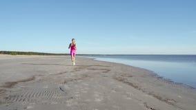 Atleta independiente de la mujer joven que corre en la playa que ejercita al corredor femenino que esprinta el entrenamiento en f almacen de video