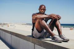 Atleta joven apto que se relaja en la pared de mar después de entrenamiento Fotos de archivo