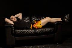 Atleta joven apto que se relaja en un sofá negro Fotos de archivo libres de regalías