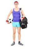 Atleta joven con el bolso de los deportes que lleva a cabo fútbol Imágenes de archivo libres de regalías