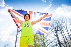 Atleta joven feliz que corre con la bandera británica Imágenes de archivo libres de regalías