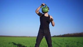 Atleta joven hermoso en ropa oscura, peso de tiros de mano a mano El peso se enrolla al aire outdoors almacen de metraje de vídeo