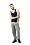 Atleta joven muscular que presenta sosteniendo el codo que mira lejos Imágenes de archivo libres de regalías