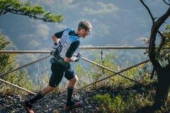 Atleta joven que corre abajo de la trayectoria de la montaña a lo largo de la cerca Fotos de archivo libres de regalías