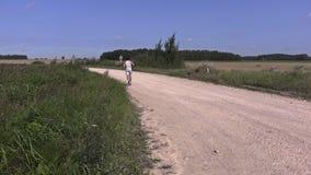 Atleta joven que corre lejos en el camino rural metrajes