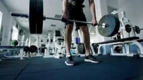 Atleta joven que hace ejercicio del deadlift con un barbell en un gimnasio almacen de metraje de vídeo
