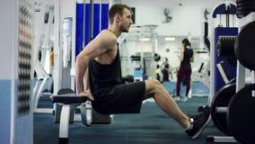 Atleta joven que hace pectorales con sus devolver detrás el suyo en un banco en un gimnasio almacen de metraje de vídeo