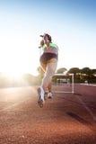 Atleta joven que salta sobre un obstáculo durante el entrenamiento en trac de la raza Foto de archivo libre de regalías