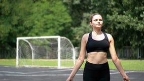 Atleta joven Woman en cuerda de salto cómoda del equipo del deporte en un campo de deportes en el parque almacen de metraje de vídeo