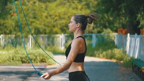 Atleta joven Woman en cuerda de salto cómoda del equipo del deporte en un campo de deportes en el parque metrajes