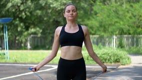 Atleta joven Woman en cuerda de salto cómoda del equipo del deporte en un campo de deportes en el parque almacen de video