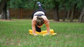 Atleta joven Woman en la yoga practicante dedicada equipo del deporte que miente en una alfombra en un parque en un césped verde almacen de metraje de vídeo