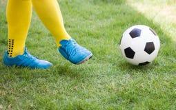 Atleta Kicking un pallone da calcio sul campo fotografia stock