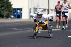Atleta lisiado en un sillón de ruedas del deporte en maratón Imagen de archivo