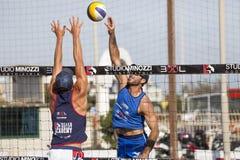 Atleta mężczyzna plażowej siatkówki obrona i kolec Ściana na sieci ręce do góry Fotografia Stock