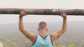 Atleta mężczyzny szkolenia prasy ćwiczenie z drewnianym barbell na zielonej halnej dolinie Sprawność fizyczna mężczyzna używa sza zbiory