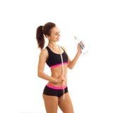 Atleta magro novo com corpo agradável no short e parte superior que guarda uma garrafa da água e de um sorriso Imagens de Stock Royalty Free