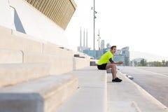 Atleta maschio in abiti sportivi luminosi che riposano dopo pareggiare attivo mentre ascoltando la musica in cuffie con area di s Immagine Stock
