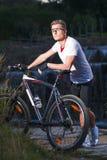 Atleta maschio caucasico con il mountain bike che posa contro la cascata fotografia stock libera da diritti