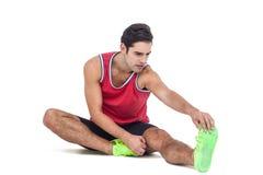 Atleta maschio che allunga il suo tendine del ginocchio Immagini Stock
