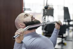 Atleta maschio che fa gli esercizi sulla macchina di pulldown nella palestra, stile di vita sano immagine stock