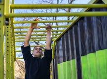Atleta maschio che oscilla sulle barre di scimmia Fotografia Stock