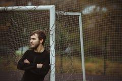 Atleta maschio che riposa sul campo di calcio Fotografia Stock
