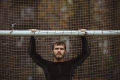 Atleta maschio che riposa sul campo di calcio Fotografie Stock