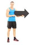 Atleta maschio che tiene una grande freccia nera che indica destra Fotografia Stock Libera da Diritti