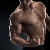 Atleta maschio di forma fisica attraente che mostra il suo bicipite Immagini Stock Libere da Diritti