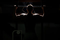 Atleta maschio Doing Pull Ups di culturismo di Siluet Fotografie Stock Libere da Diritti