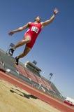 Atleta maschio Doing un salto in lungo Fotografia Stock Libera da Diritti