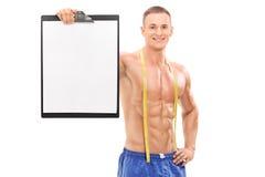 Atleta maschio senza camicia che tiene una lavagna per appunti Immagini Stock