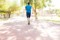 Atleta maschio Sprinting On Road in parco fotografia stock libera da diritti