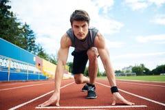 Atleta masculino aproximadamente para começar uma sprint olhar a câmera imagem de stock