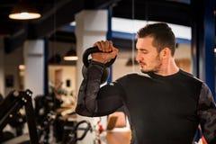 Atleta masculino atrativo que faz o exercício do bíceps com peso imagem de stock royalty free