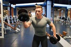 Atleta masculino atrativo que faz o exercício do bíceps com pesos imagens de stock royalty free