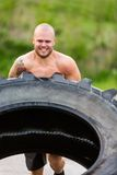 Atleta masculino Doing Tire-Flip Exercise Foto de Stock Royalty Free