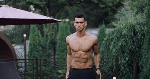 Atleta masculino muscular atrativo que faz o exercício com saltos e mãos dos balanços no jardim home 4k HD vídeos de arquivo