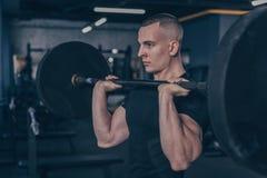 Atleta masculino muscular que dá certo com o barbell no estúdio do gym imagens de stock royalty free