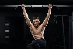 Atleta masculino muscular que levanta na barra horizontal no gym escuro imagem de stock