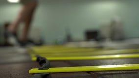Atleta masculino novo Makes Quick Jumps ao longo da escada de corda vídeos de arquivo