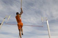 Atleta masculino Performing um salto com vara  Imagens de Stock