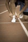 Atleta masculino que amarra laços para movimentar-se Homem que movimenta-se em uma pista de atletismo fotos de stock