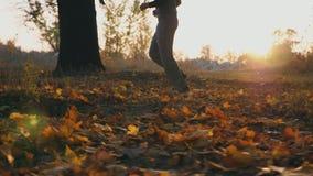Atleta masculino que corre atrav?s do parque do outono que pisa nas folhas ca?das secas Forma??o do indiv?duo exterior no tempo d filme