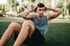 Atleta masculino que faz exercícios na imprensa exterior fotografia de stock royalty free