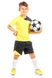 Atleta menor de sexo masculino que lleva a cabo un fútbol Foto de archivo libre de regalías