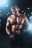 Atleta muscolare che posa con la testa di legno nella palestra di sport Fotografia Stock